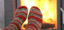 Füße in dicken Socken vor dem Kaminfeuer (Foto)
