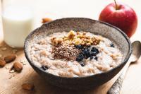 Foto von einem Porridge in einer Schüssel, im Hintergrund ein Apfel und ein Glas Milch