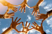 Hände vor einem Himmel als Symbol von Zusammenhalt