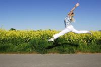 Eine Frau macht vor einer Blumenwiese einen Sprung. (Foto)