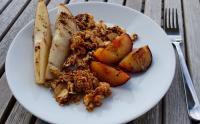 Foto von einem Teller mit Birnenspalten, Zwetschgenspalten und Hafercrumble aus dem Ofen