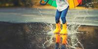 Foto eines Kindes, das in Gummistiefeln in eine Pfütze springt (Quelle: Fotolia)