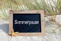 """Holzschild """"Sommerpause"""" auf weißem Sand mit Gras"""
