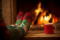 Foto von Füßen in warmen Socken vor einem Kaminfeuer