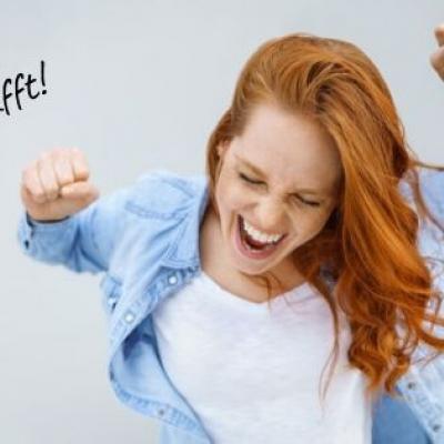 Foto einer Frau, die ihre Arme in der Höhe hat und sich freut und lacht