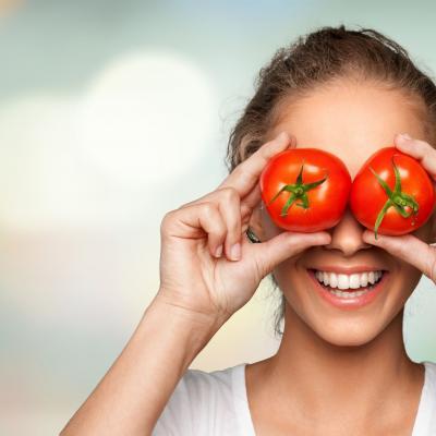 Foto einer lachenden Frau, die sich zwei Tomaten über die Augen hält