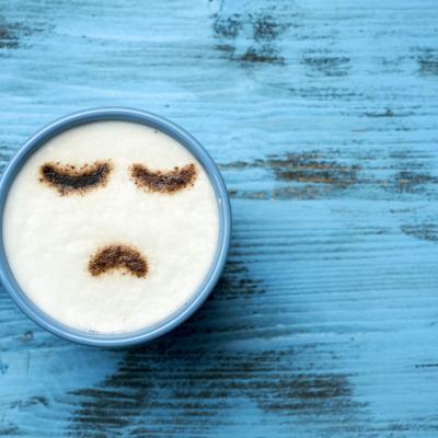 Foto einer Tasse Cappuccino mit einem traurigen Gesicht im Milchschaum auf blauem Tisch