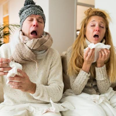 Foto von einem Mann und einer Frau mit Taschentüchern und Schal, kurz vor einem Niesen