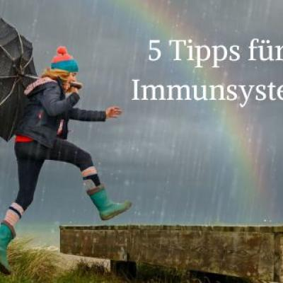 Foto einer Frau in Gummistiefeln und mit Regenschirm, die auf einen Holzsteg springt, dahinter ein Regenbogen