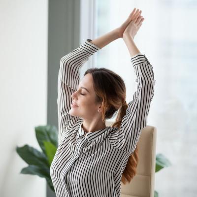 Foto einer Frau in Bluse, die ihre Arme nach oben dehnt und sich entspannt