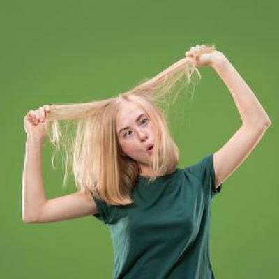 Foto einer Frau, die sich die Haare weghält und verwirrt schaut (Fotolia), vor grünem Hintergrund