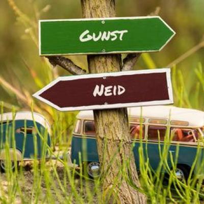 """2 Verkehrsschilder - """"Gunst"""" und """"Neid"""". Wohin geht die Richtung?"""