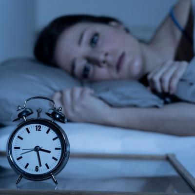 Foto einer Frau, die wach im Bett liegt, davor der Wecker auf 3.30 Uhr