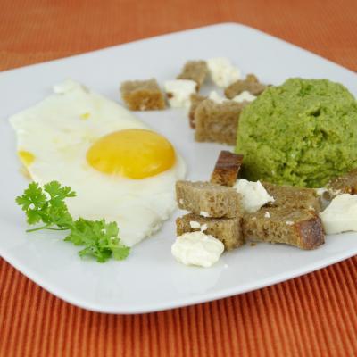 Foto von einem weißen Teller mit einem Spiegelei, Brokkolimus, Brotwürfeln und Fetastücken und etwas Petersilie
