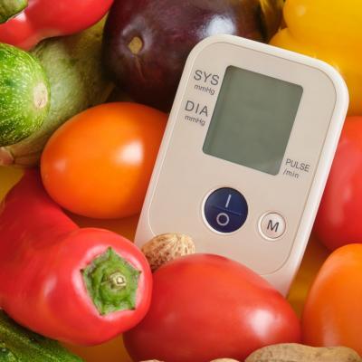 Foto eines Blutdruckmessers umgeben von Tomaten, Paprika und anderem Gemüse