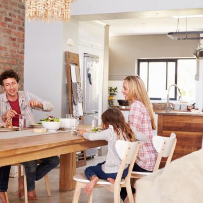 Foto von Mann, Frau und zwei Kindern an einem Holztisch beim Essen
