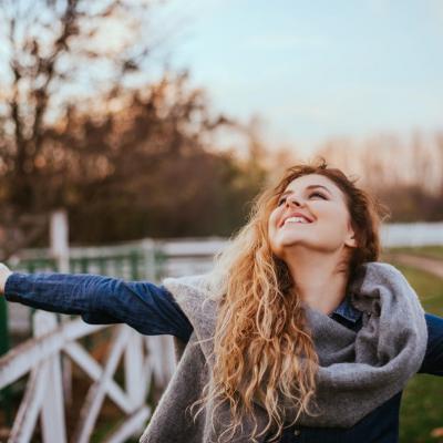Foto einer Frau, die lachend und mit geöffneten Armen auf einer Wiese steht, mit Pullover und Schal