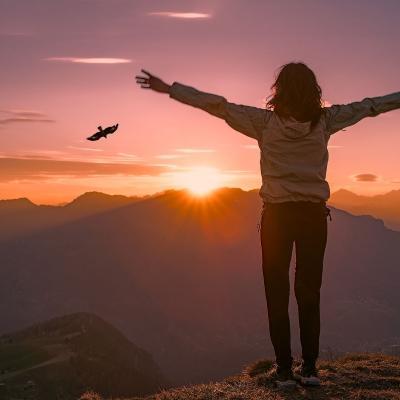 Foto einer Frau mit zum Himmel erhobenen Armen, von hinten, am Berggipfel bei Sonnenaufgang, am Himmel ist ein großer Vogel zu sehen