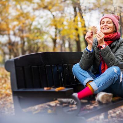 Foto einer Frau, die vor einem Herbstwald am Boden sitzt, mit buntem Schal und Mütze, und lachend ein Blatt ansieht