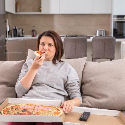 Foto einer Frau, die am Sofa sitzt und Pizza aus einem Karton isst