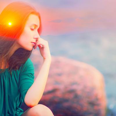 Foto einer Frau, die am Meer sitzt. Ein Sonnenstrahl trifft ihren Kopf. Sie hat eine grüne Bluse und die Augen geschlossen.