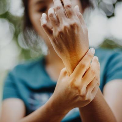 Foto einer Frau, die sich ihr Handgelenk mit der anderen Hand hält