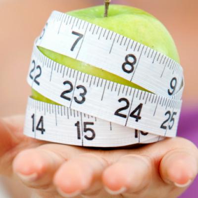 Ein Maßband um einen Apfel herum als Symbol für Diäten