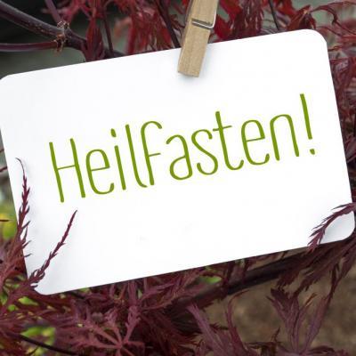 Ein weißes Schild, auf dem Heilfasten steht, auf roten Ästen liegend.