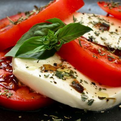 Foto von Mozzarella, Tomaten und Basilikum mit Gewürzen