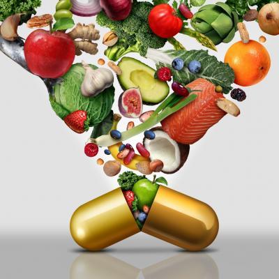 Bild von Gemüse, Obst, Fisch, die in Form eines Trichters in eine große, goldene Pille gegossen werden