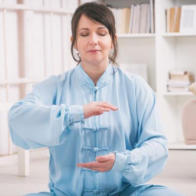 Foto einer Frau mit geschlossenen Augen, die Qi Gong macht und ihre Hände übereinanderhält