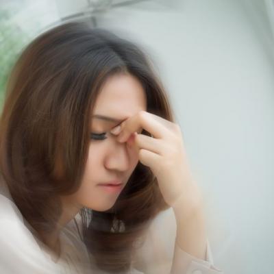 Foto einer Frau, die sich die Hand an die Stirn hält (von  Fotolia)