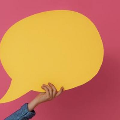 Eine gelbe Sprechblase, die von einer Hand gehalten wird, vor rotem Hintergrund. (Fotolia)