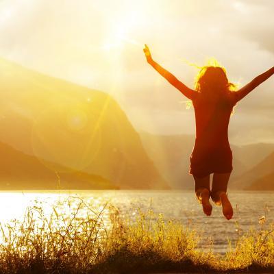 Foto von einer Frau, die mit hoch erhobenen Armen in einen See springt, im Sonnenuntergang