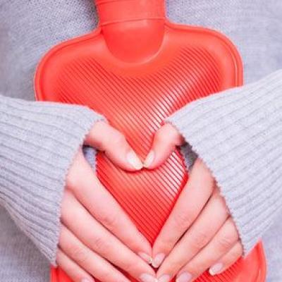 Wärmeflasche (Thermofor) am Bauch (Foto), gehalten von 2 Händen