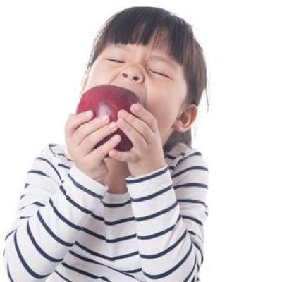Foto eines Mädchens, das in einen Apfel beißt (Fotolia)